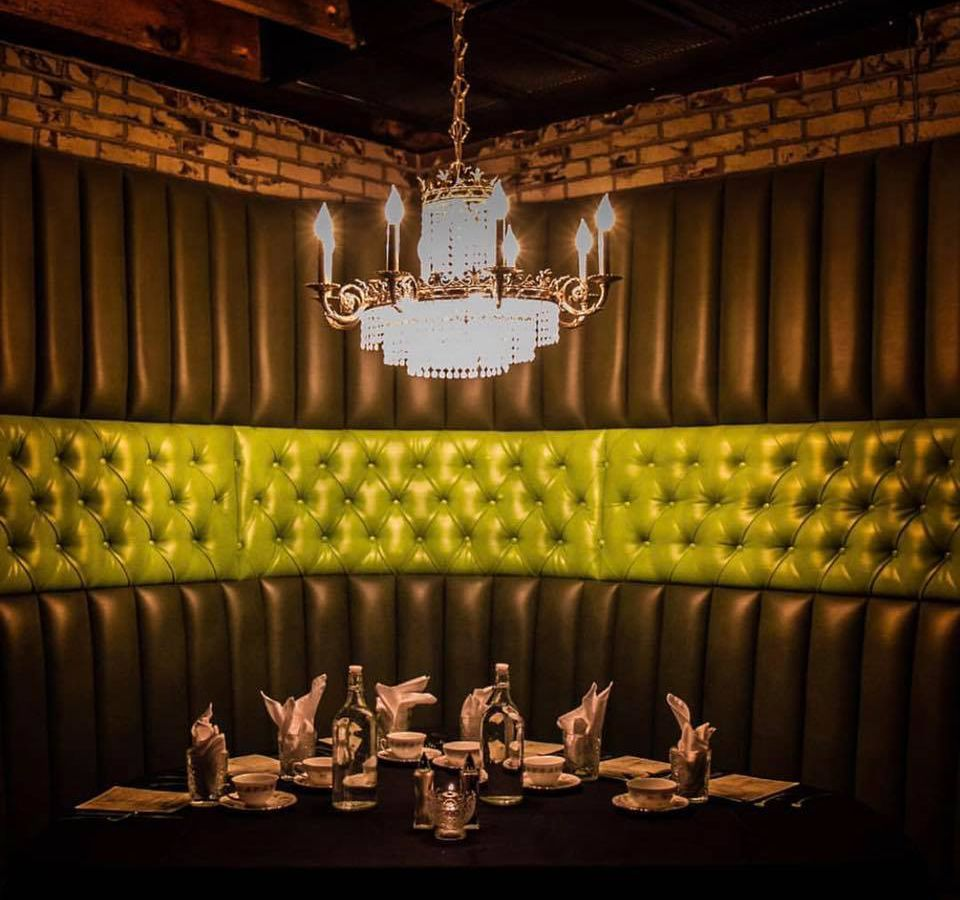 A large lime-green backed, curved booth under a crystal chandelier is set for service