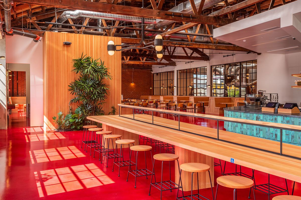 A bright red cafe with wooden communal stools and house plans.