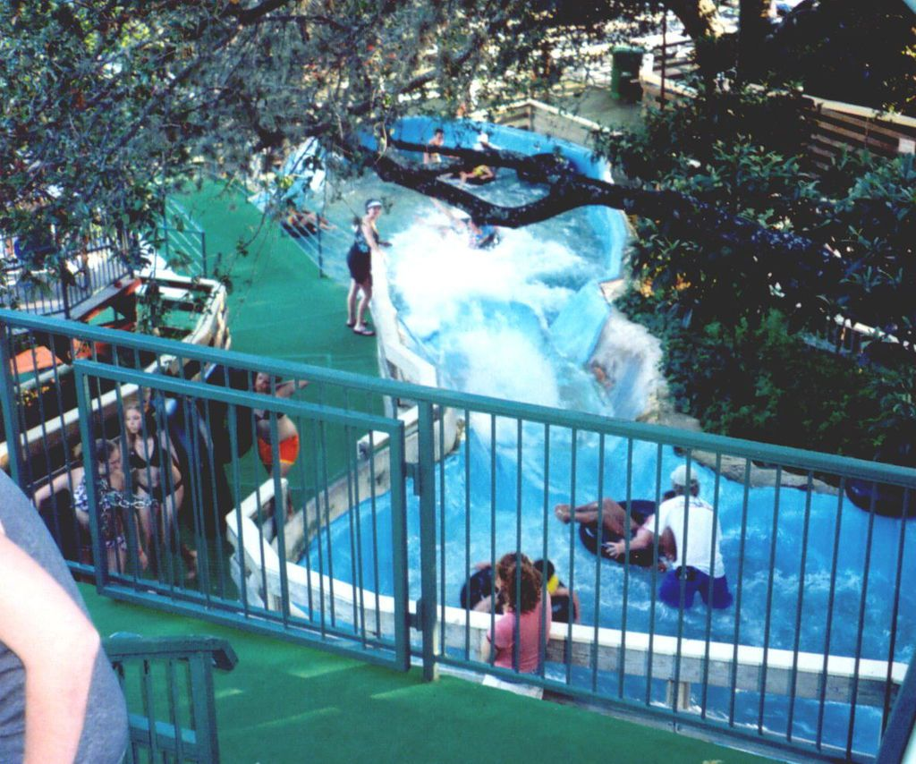 A waterpark slide. The water is from a nearby river. There are people in the water on the slide.