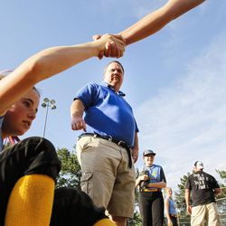 Brad Thomas, middle, who has been coaching his daughter's accelerated softball team for the past five years, checks on a injured player during a scrimmage at Dewey Bluth Park in Sandy, Utah, Thursday, June 9, 2016.