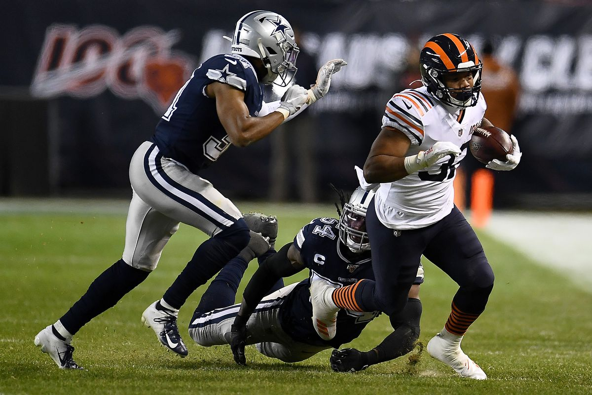 Bears running back David Montgomery drags a Cowboys player with him last Thursday.