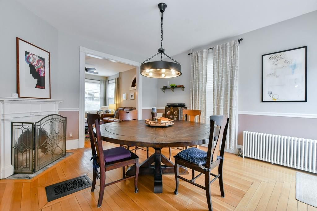 A dining room with a table and chairs in front of a fireplace.