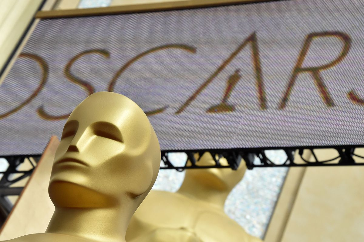 a close-up of a giant Oscar statue with an Oscars sign behind it