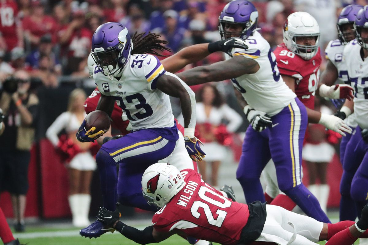 Minnesota Vikings running back Dalvin Cook (33) breaks a tackle by Arizona Cardinals cornerback Marco Wilson (20) during the first quarter in Glendale, Ariz. Sept. 19, 2021.