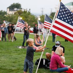 A child holds an American flag ahead of a vigil to honor the life and service of Marine Staff Sgt. Taylor Hooverat the Capitol in Salt Lake City on Sunday, Aug. 29, 2021. Hoover was one of the 13 U.S. service members killed by the terrorist attack at Hamid Karzai International Airport in Kabul, Afghanistan.
