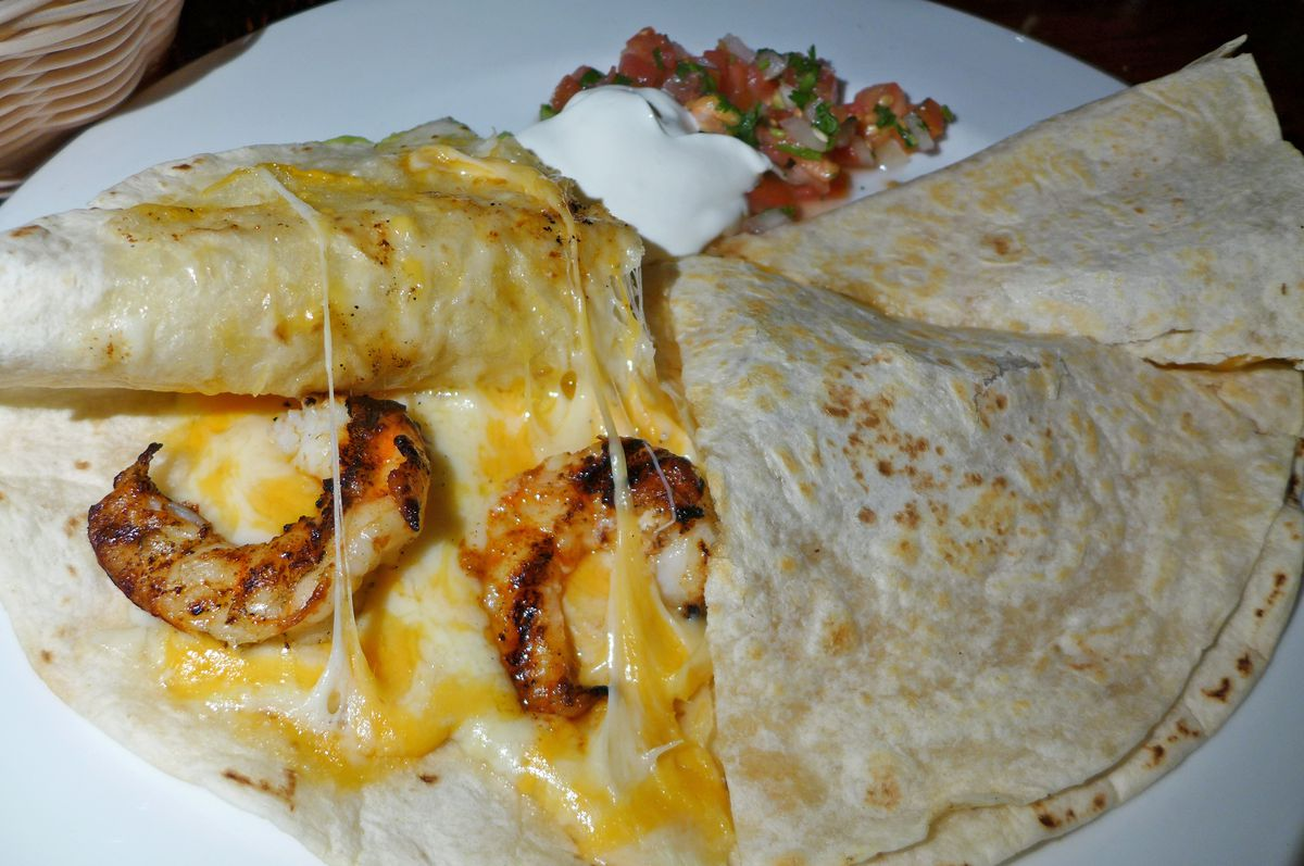 Two flour tortillas glued together with cheese, with the top flap of one pulled back to review two grilled shrimp.