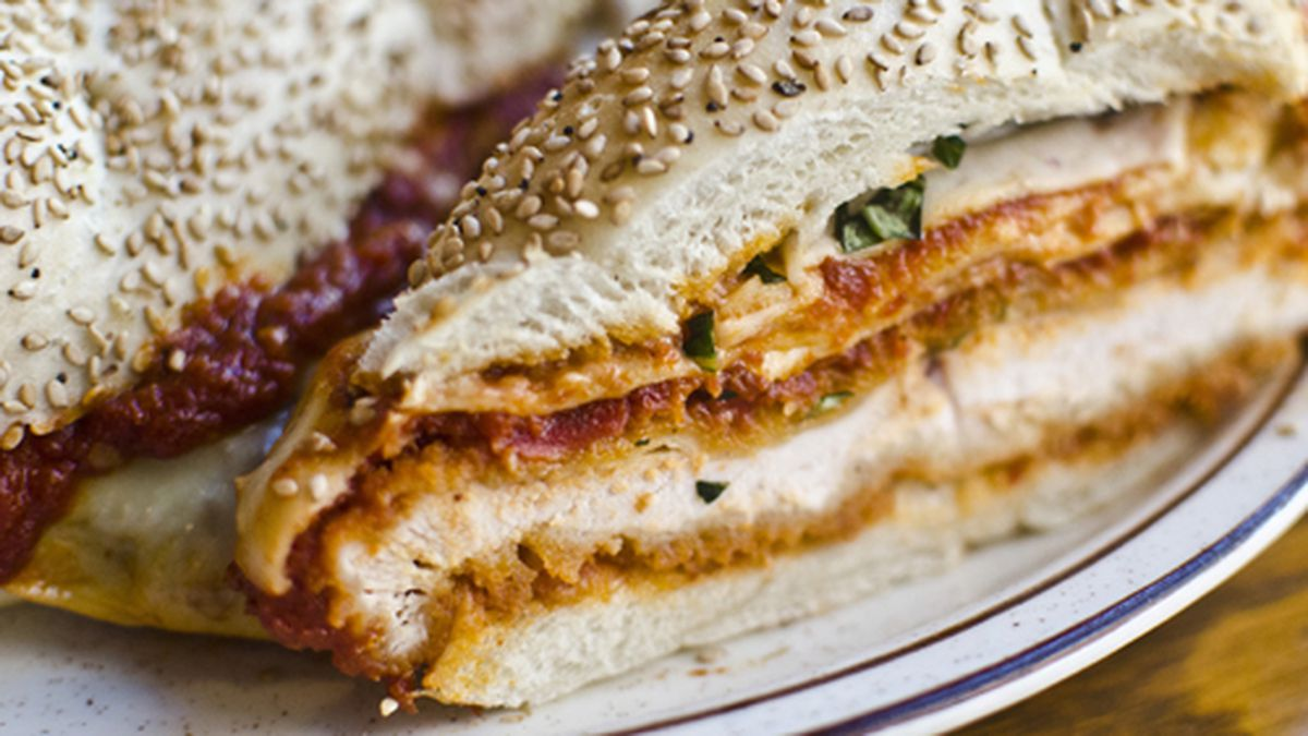 A sesame-studded bun loaded with chicken parmesan cut diagonally
