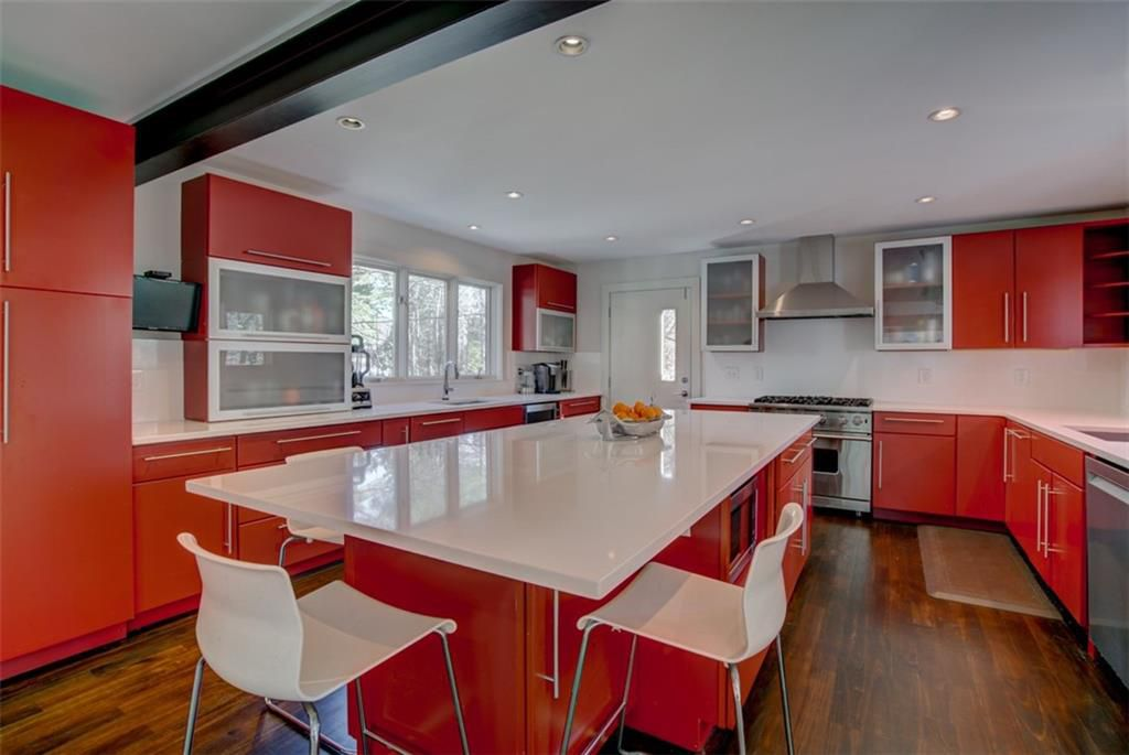 A large kitchen with a steel beam overhead and red cabinetry and white countertops.