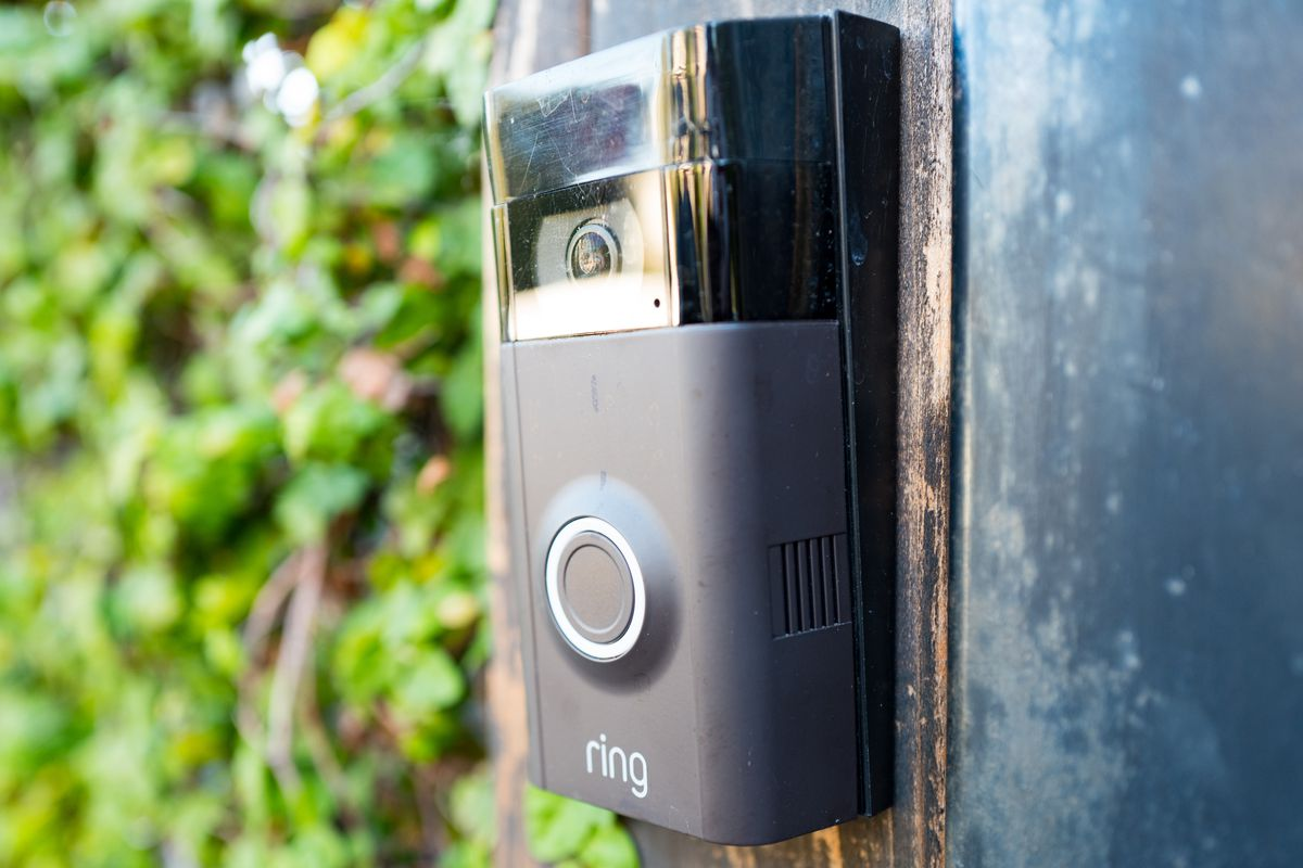 A Ring doorbell on the wall of a house's front porch.