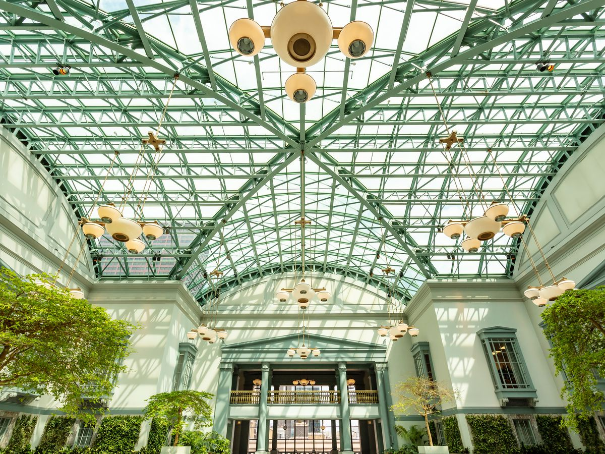 A metal and glass ceiling of a wintergarden. There are light fixtures hanging down above planted indoor trees.