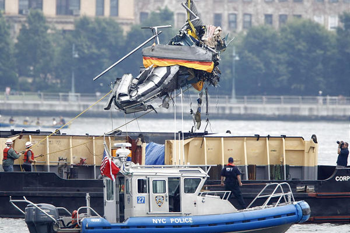 The wreckage of a helicopter is lifted by crane from the Hudson River and placed on a boat Sunday.