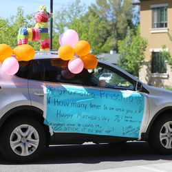 A decorated car drives past as families wave and cheer residents at The Ridge Cottonwood senior living center in Holladay during a Mother's Day parade on Saturday, May 9, 2020.