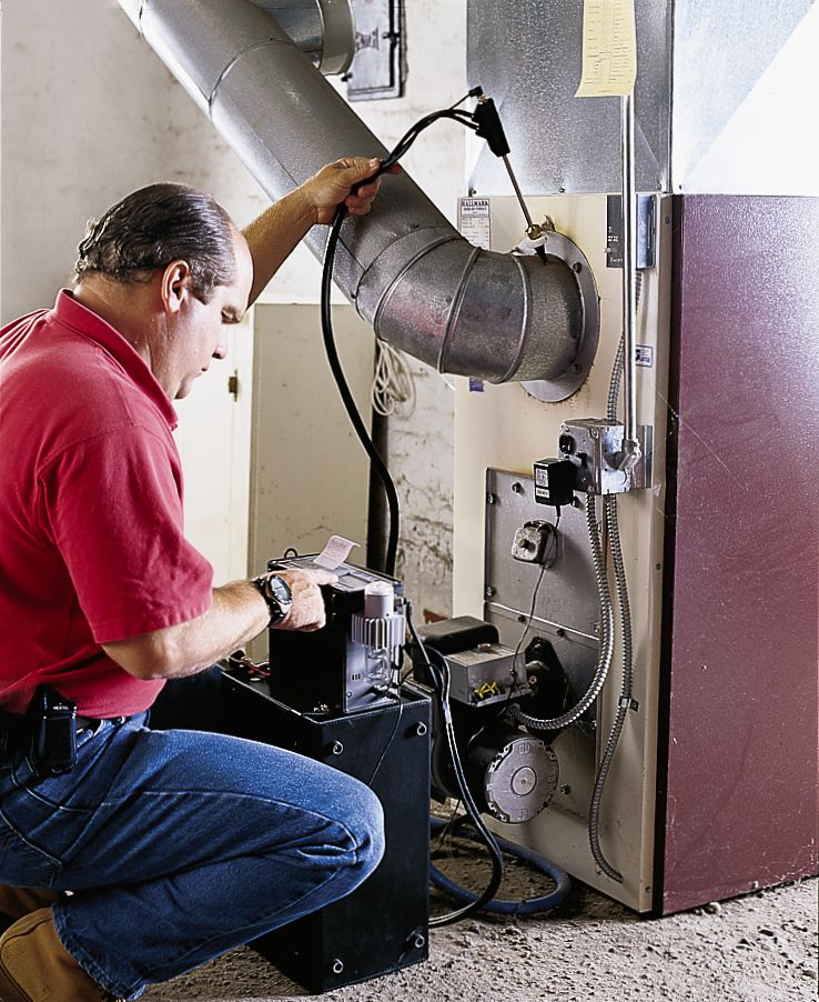 Person kneeling down by a burner to see if the furnace is in good condition.