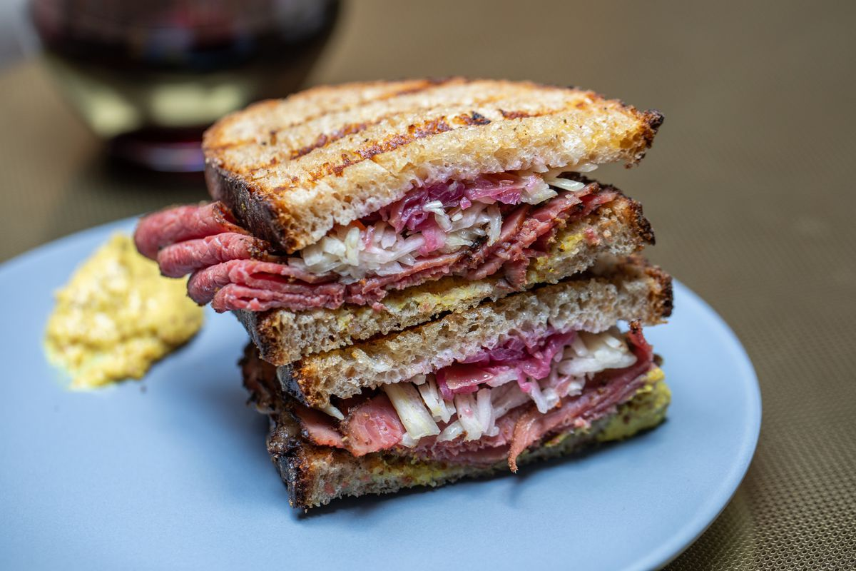Two halves of a pastrami Reuben sandwich sit on a blue plate, with a smear of mustard in the background