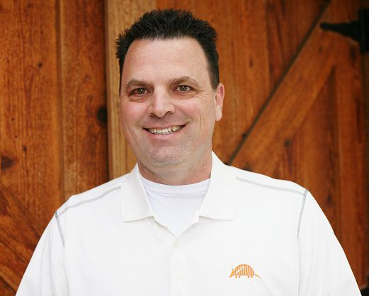 Keith Todd Ashley stands in white polo shirt with Nine Band Brewing logo on lapel