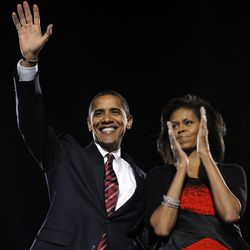 Barack Obama waves beside wife Michelle during his election night victory rally at Grant Park. | Emmanuel Dunand/AFP/Getty Images