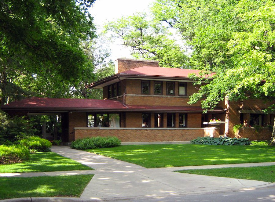 The exterior of the Harry S. Adams house. The facade is red brick. The house is surrounded by trees.