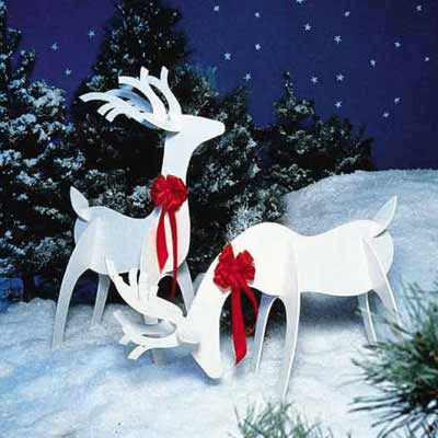 Two wooden reindeer with red bows on their necks used as yard decoration.