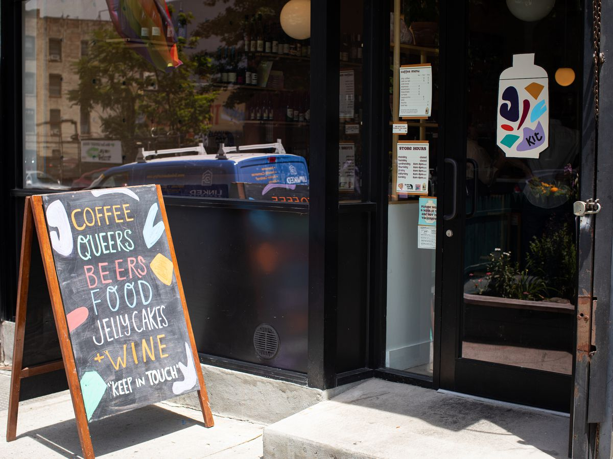 """The exterior window of a restaurant with a chalkboard sandwich sign on the sidewalk that reads """"Coffee, Queers, Beers, Food, Jelly Cakes, and Wine. Keep in Touch"""""""