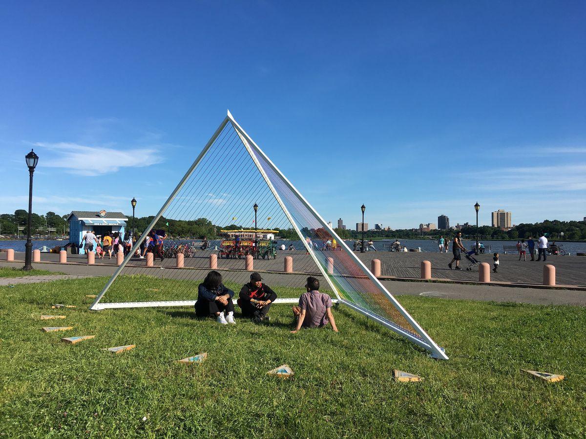 Three individuals under a triangular art installation in a park.
