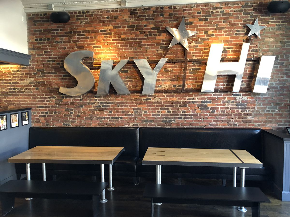 """A metal sign reading """"Sky Hi"""" hangs on a brick wall above two wooden tables and black booths"""
