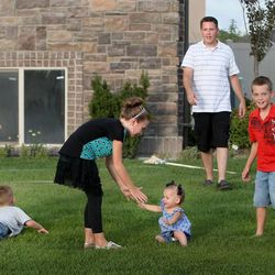 The Hyde family, Dax, left, Gabe, Will, Laryn, Hazel, Trent, Davis, Camilla and Hattie, plays outside at their home in Syracuse on Thursday, Aug. 1, 2013.