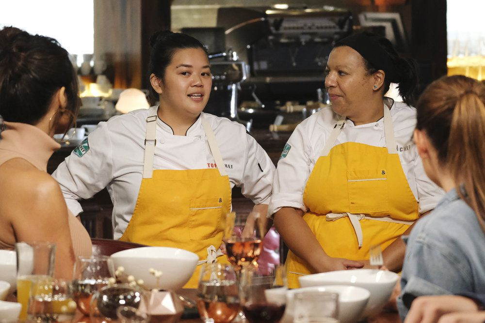 Two women with yellow aprons talk