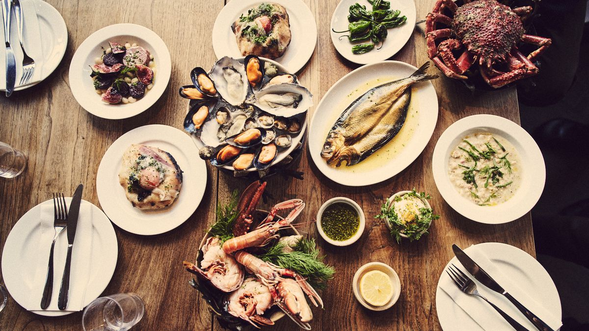 A table laid with brunch dishes from Brat in Shoreditch — mussels and oysters; a grilled whole fish; lardo and egg yolk flatbreads; crabs; blistered peppers; langoustines
