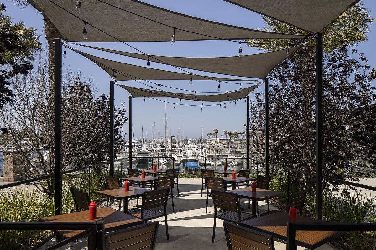A breezy waterside patio for a new restaurant, with boats beyond.