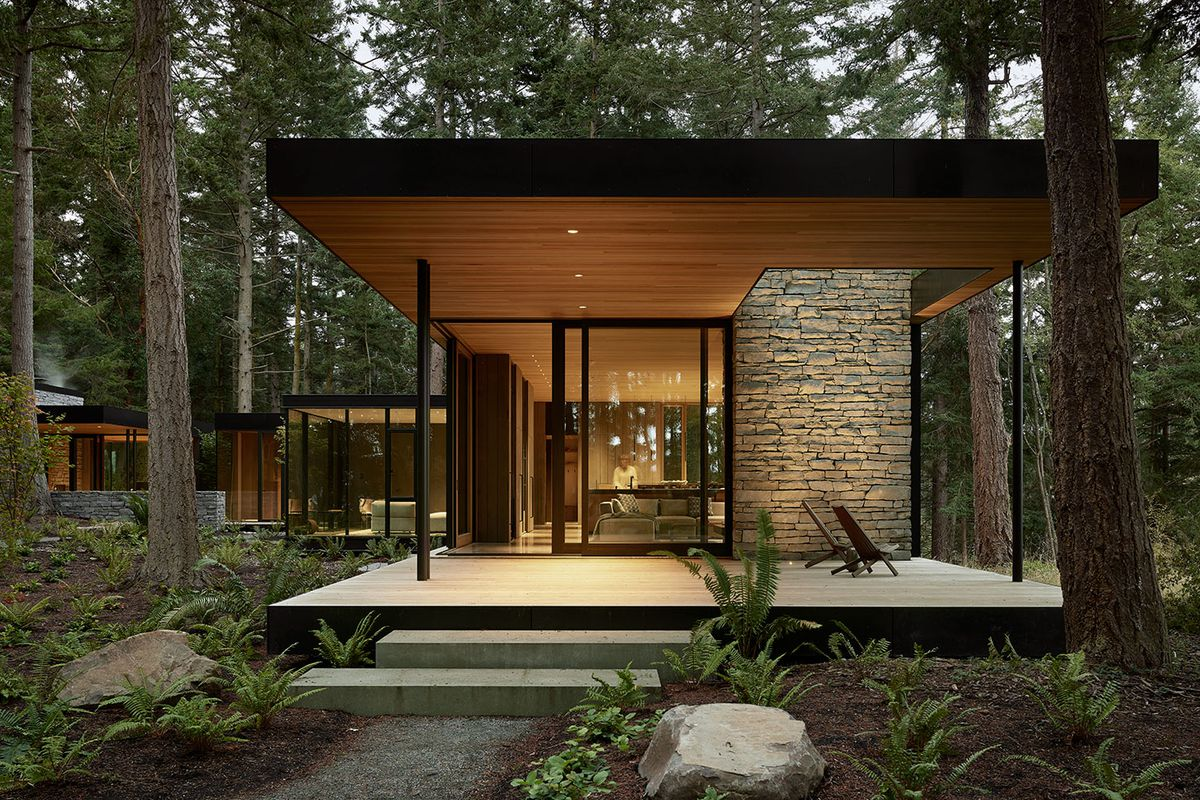 Exterior of house in woods with glass walls.