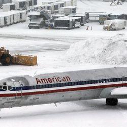 A snowplow works at Salt Lake City International Airport, Thursday, Dec. 19, 2013.