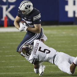 Brigham Young Cougars tight end Hank Tuipulotu (35) runs by Texas State Bobcats safety Kevin Anderson (5) in Provo on Saturday, Oct. 24, 2020.