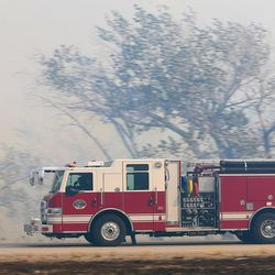 A firetruck races westbound on I-84 as fire burns homes and property near Weber Canyon on Tuesday, Sept. 5, 2017.
