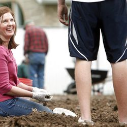 Tammy Stephan smiles up at her son Austin as they gather rocks out of the garden ground. Members of the Orem Community Church, the Orem 4th Ward of the LDS Church and the Assemblies of God work together Monday, April 30, 2012 to remove rocks from the ground in the garden area. The groups are working together to plant, cultivate, and harvest a garden, the produce from which will be donated to the Food & Care Coalition.