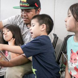 Uncle Eduardo Guzman reading to Isabella, Mathew and Abigail Alvarez at the Dee Events Center in South Ogden on Tuesday, Sept. 5, 2017.