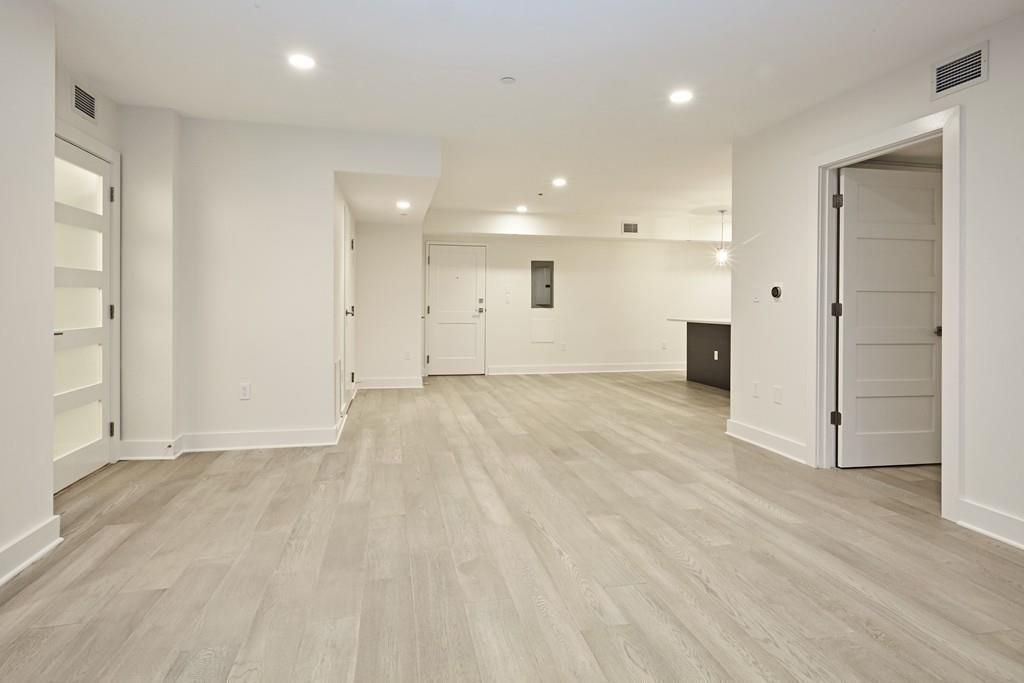 A large, empty living room-dining room in a newly done condo.