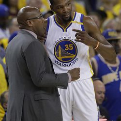 Golden State Warriors forward Kevin Durant (35) talks with interim head coach Mike Brown during the first half of Game 1 of basketball's NBA Finals against the Cleveland Cavaliers in Oakland, Calif., Thursday, June 1, 2017.