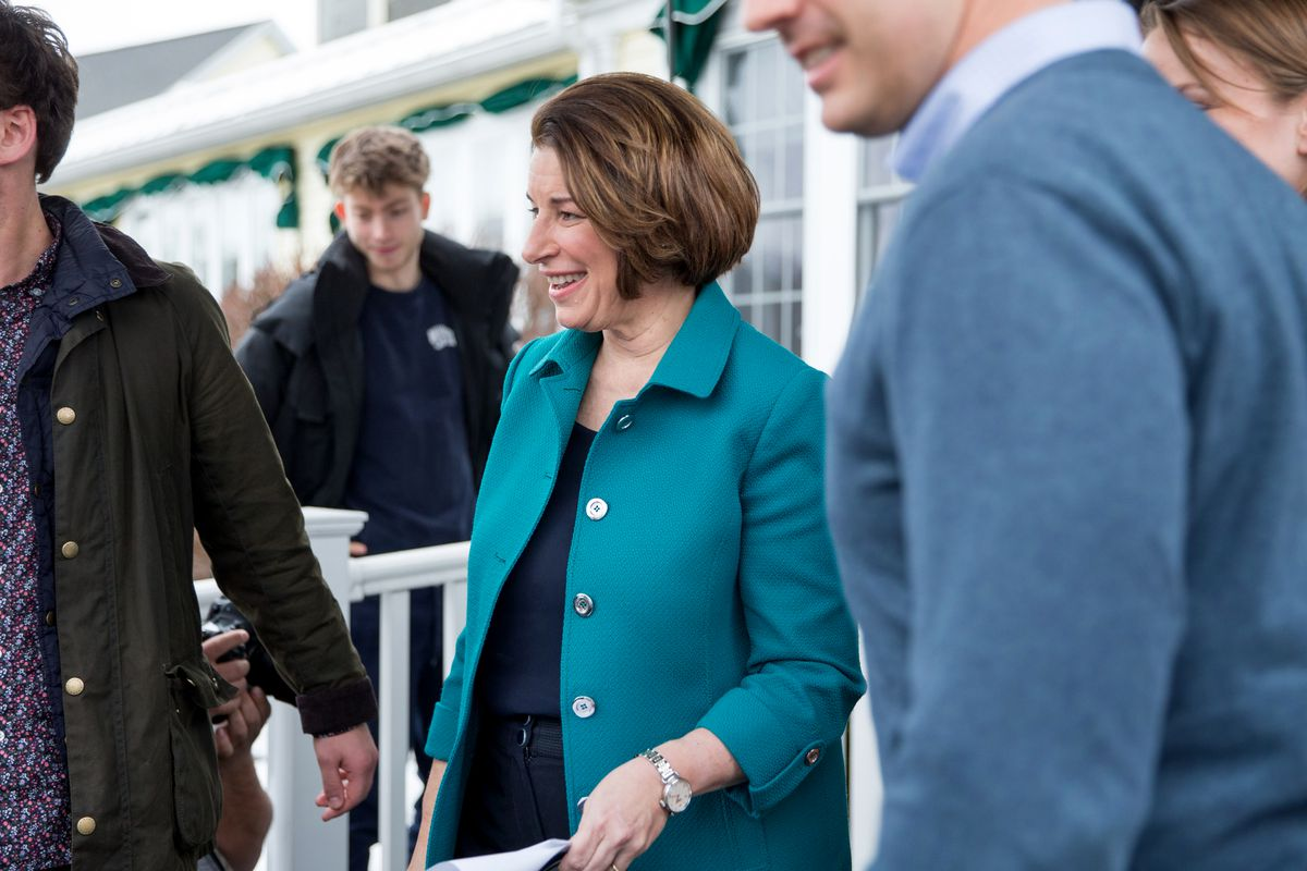 Sen. Amy Klobuchar, smiling, seen in profile, with others leaving a campaign event.