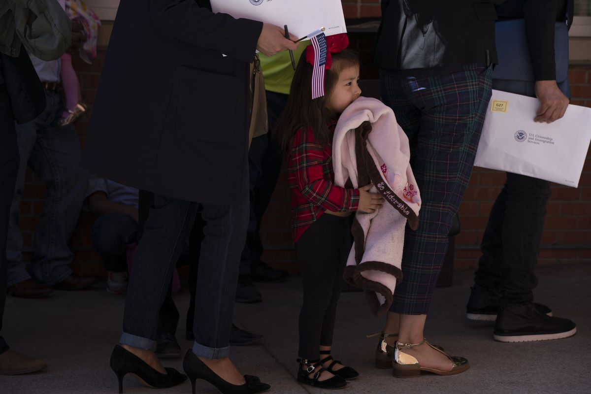 A little girl holding a blanket stands in line with surrounding adults.