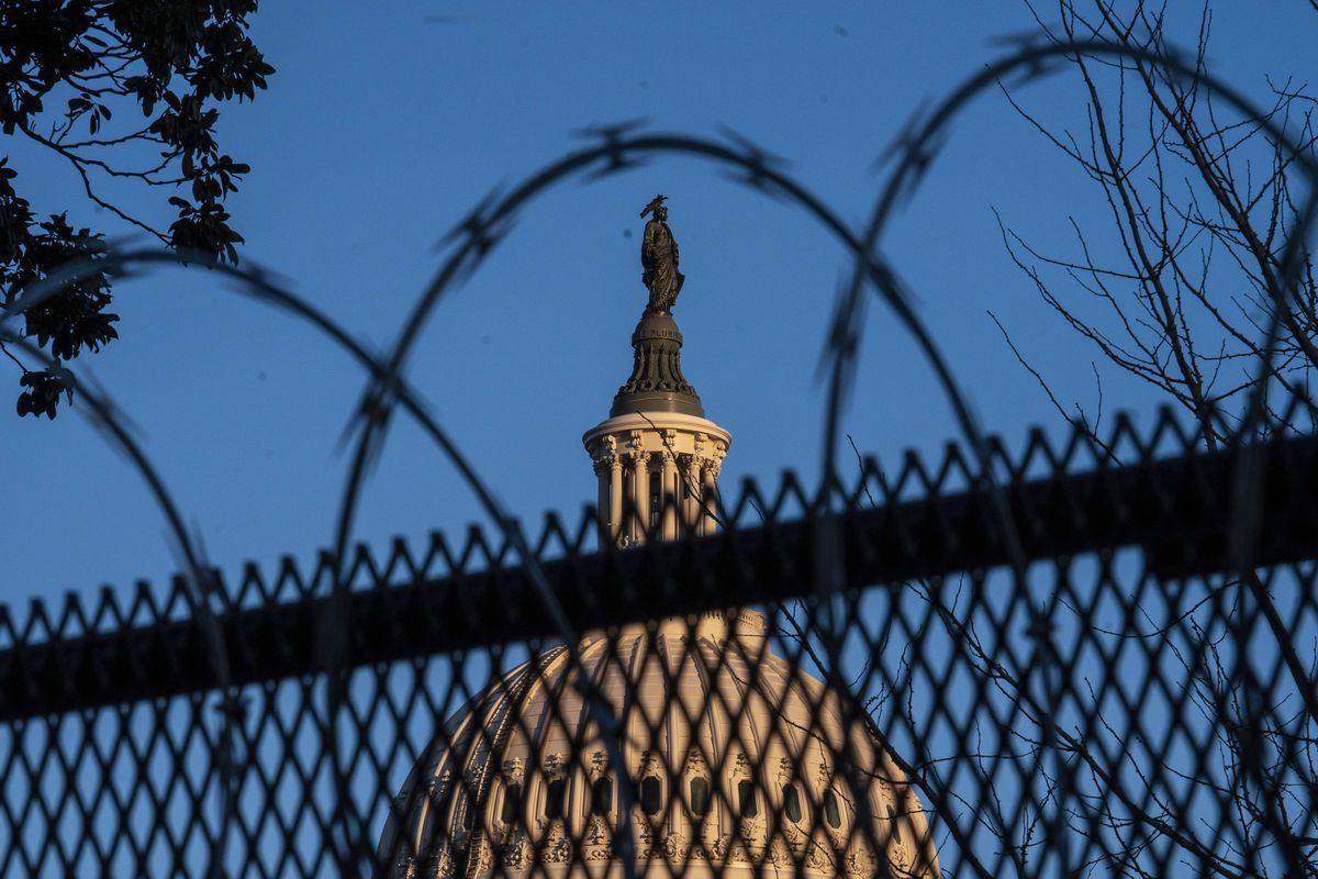 The top of the US Capitol building seen through a razor-wire-topped fence.