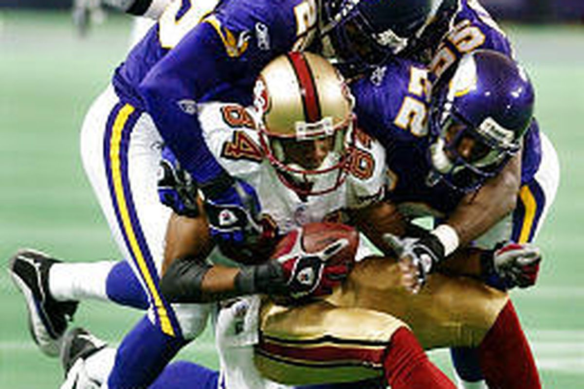 San Francisco receiver Cedric Wilson gets crunched by three Minnesota defenders during Vikings' 35-7 victory Sunday.