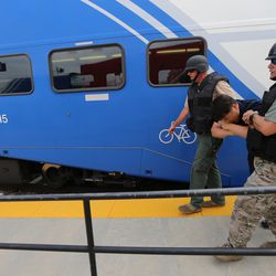 """Members of a bomb squad assist a """"victim"""" off a FrontRunner train during """"Hell on Wheels,"""" a full-scale, two-day, emergency protection and response drill at the Salt Lake Central Station on Tuesday, Aug. 8, 2017. The drill included emergency personnel from the Utah Transit Authority, the FBI, Salt Lake County Emergency Management, the West Valley and Salt Lake City fire departments, University of Utah Emergency Management, the University of Utah Police Department, Amtrak, Union Pacific, Murray Victim Advocates and Utah State Medical Examiner's Office. The drill simulated multiple terrorists entering the Salt Lake Valley and dividing up."""