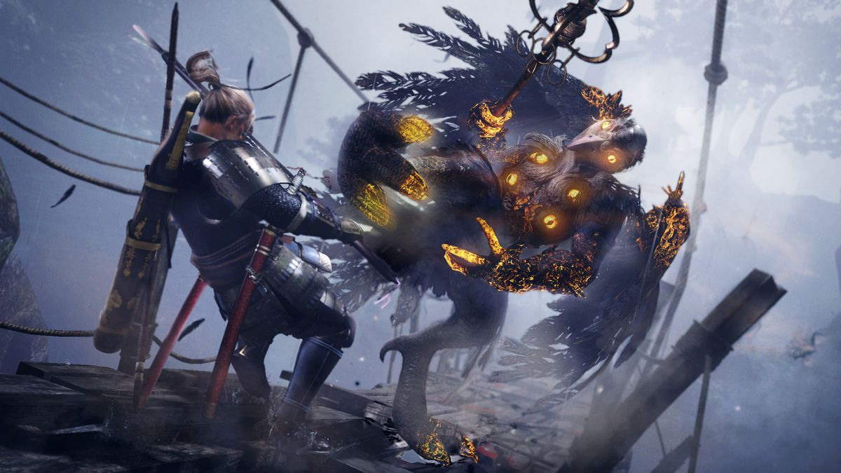 In this Nioh screenshot, protagonist William is facing off against a winged enemy known as a tengu on a rickety bridge. The tengu carries a large staff, and one of its legs are raised, kicking at William. William is lurching backward, possibly stunned by