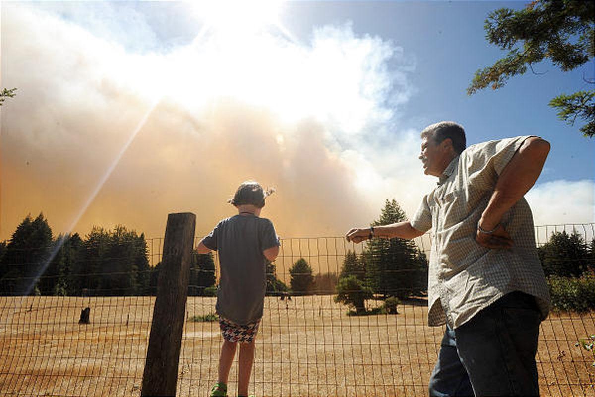 Bonny Doon residents watch as smoke billows over a field in Santa Cruz County, Calif., on Thursday.