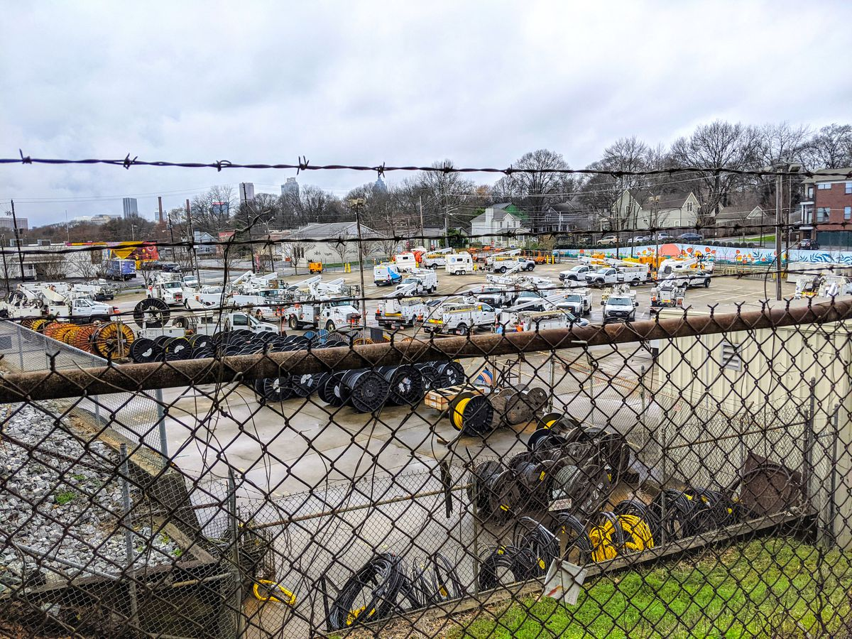 A large parking lot with white vehicles and wire spools.