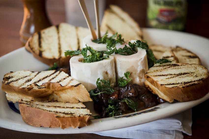 Roasted bone marrow with toasted bread on a white plate