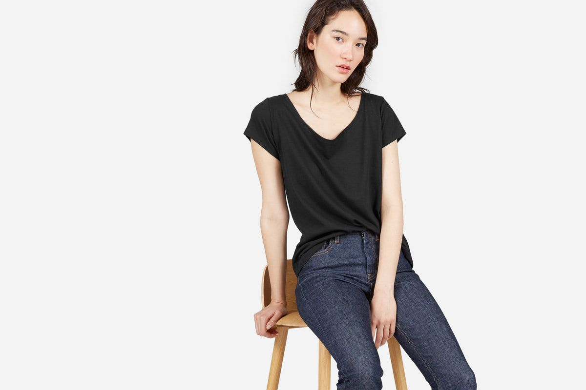 A model in a black T-shirt and jeans sitting on a stool