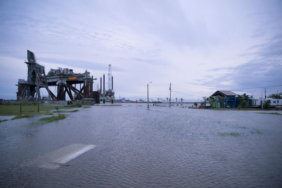 What looks as if it was once a street is covered in water; a chemical plant and small building look like islands in a sea. In the foreground of the photo, detritus is visible under the water.