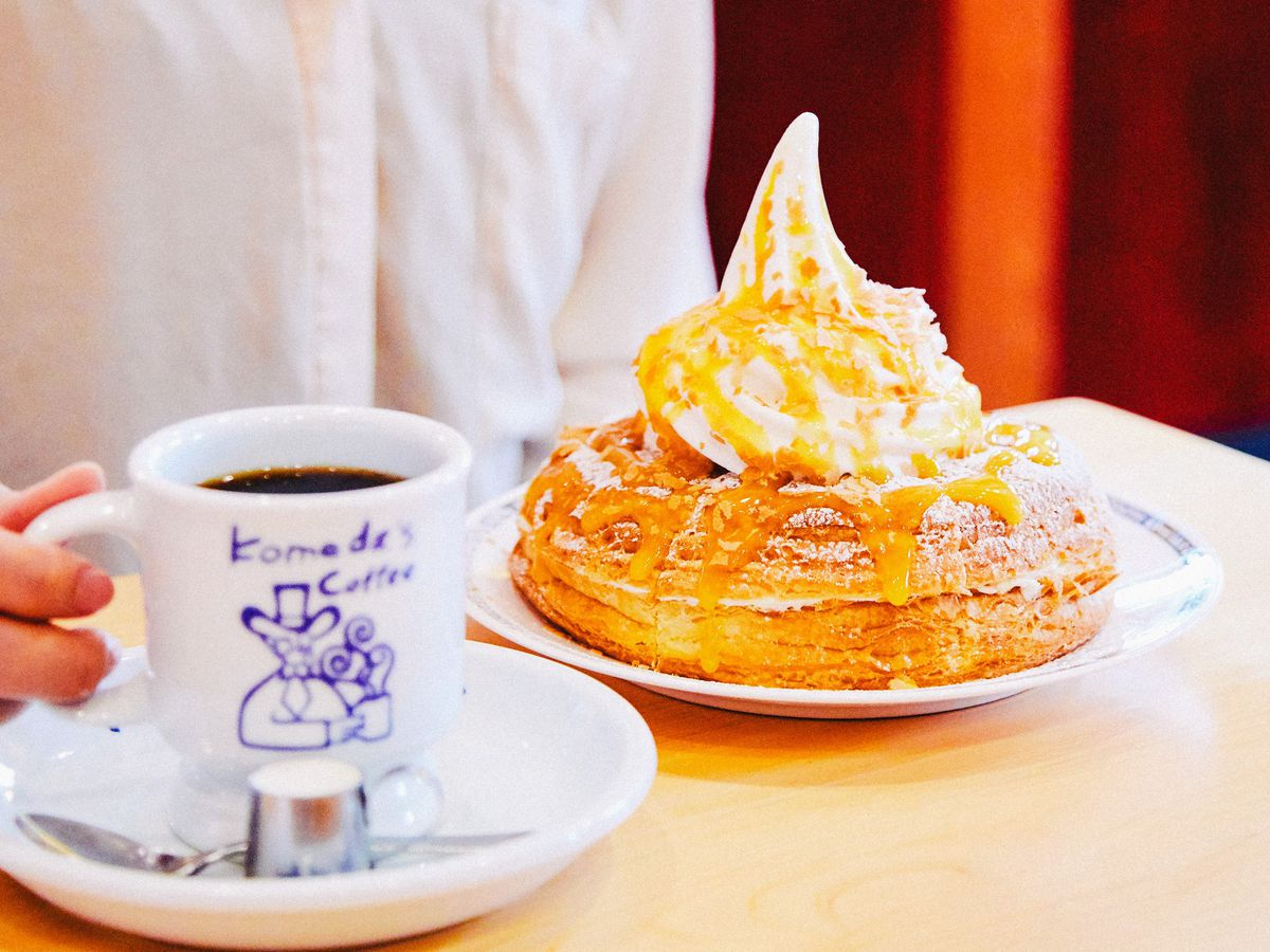 A customer sits at a small table with a cup of coffee in hand (in a branded coffee mug) with a large pastry topped with a swirl of soft serve ice cream
