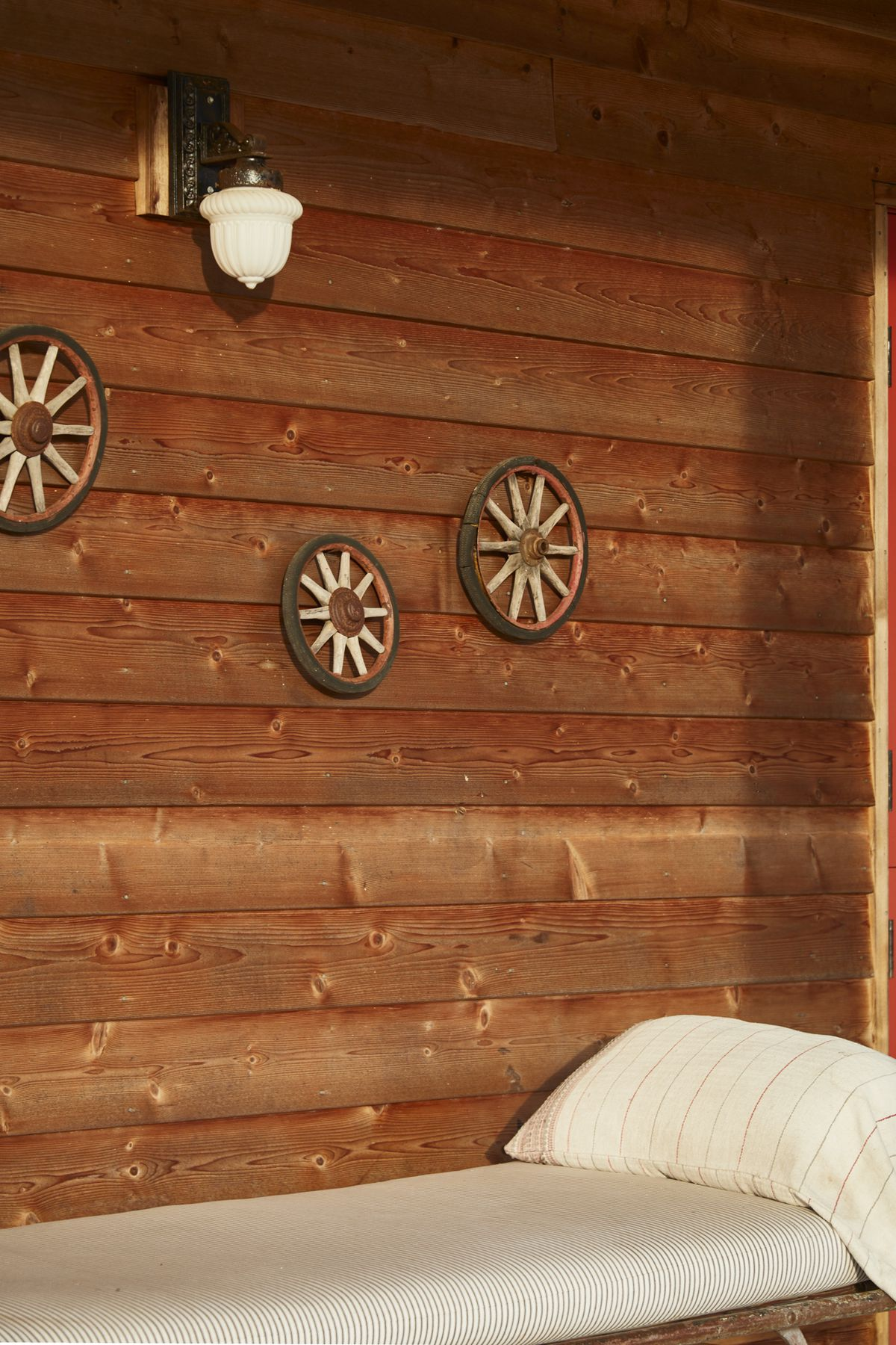 Another detail shot shows the wood siding on the guest wing. Small wagon wheels and an antique light fixture decorate the walls.